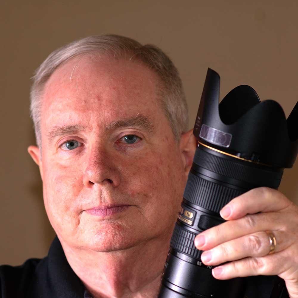 Greg Woods holding a large camara lens